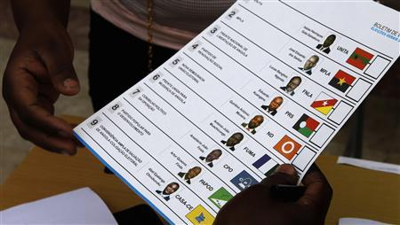 An election official hands a ballot paper to a voter during national elections in the capital Luanda, August 31, 2012. REUTERS/Siphiwe Sibeko