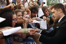 "U.S. actor Zac Efron signs autographs as he arrives on the red carpet for the world premiere of his movie ""At Any Price"" at the 69th Venice Film Festival in Venice August 31, 2012. REUTERS/Max Rossi"