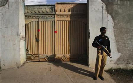 A policeman keeps guard outside the gates of the compound where al Qaeda leader Osama bin Laden was reported to have been killed in Abbottabad May 4, 2011. REUTERS/Faisal Mahmood