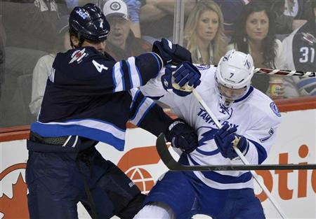 Winnipeg Jets' Zach Bogosian (L) is checked by Tampa Bay Lightning's Brett Clark during the first period of their NHL hockey game in Winnipeg April 7, 2012. REUTERS/Fred Greenslade