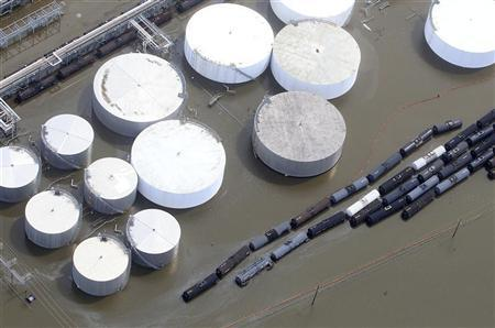 Oil storage containers are partially submerged in flood waters after a Hurricane Isaac levee breach in Braithwaite, Louisiana August 31, 2012. REUTERS/Sean Gardner