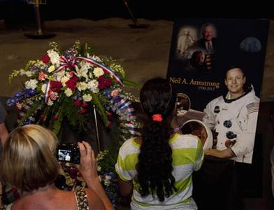 People take pictures during a memorial service for Neil Armstrong in the Apollo Saturn V Center at Kennedy Space Center, Florida August 31, 2012. U.S. astronaut Armstrong, who took a giant leap for mankind when he became the first person to walk on the moon, has died at the age of 82, his family said on August 25, 2012. Attendees of the three minute ceremony toured the space center after paying their respects for Armstrong. REUTERS/Michael Brown