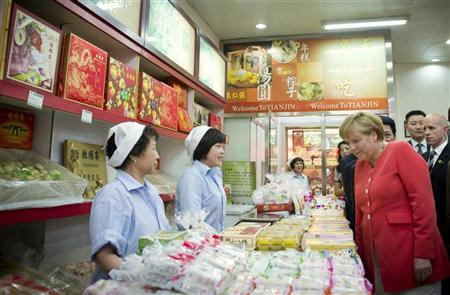 German Chancellor Angela Merkel (R) visits a stand in the Food Street in the city of Tianjin, just outside of Beijing, August 31, 2012. REUTERS/Bundesregierung/Guido Bergmann/Pool