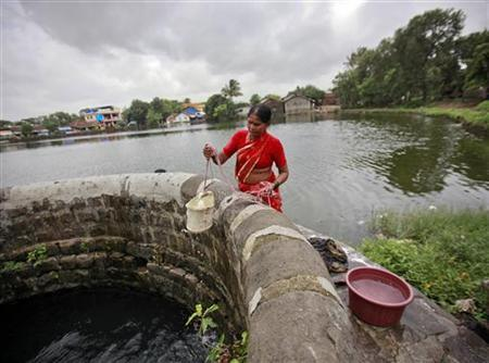 A woman fetches water from a well at Pargoan village, the proposed site of Navi Mumbai airport, about 45 km east of Mumbai August 8, 2012. REUTERS/Danish Siddiqui