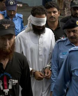 Police escort blindfolded Muslim cleric Khalid Jadoon as he is brought before a judge at a court in Islamabad September 2, 2012. REUTERS/Faisal Mahmood