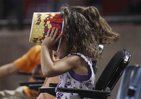 A young baseball fan makes sure there's not a kernel of popcorn left as she watches the Chicago Cubs play the Arizona Diamondbacks during their MLB National League baseball game in Phoenix, Arizona, June 24, 2012. REUTERS/Darryl Webb