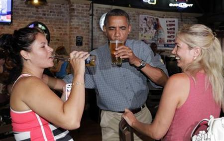 U.S. President Barack Obama enjoys a beer with Jennifer Klanac (L) and Suzanne Woods (R) at Ziggy's Pub in Amherst, Ohio July 5, 2012. REUTERS/Kevin Lamarque