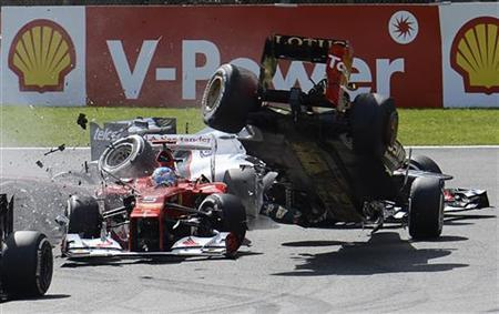 Lotus Formula One driver Romain Grosjean (R) of France crashes with Ferrari Formula One driver Fernando Alonso (L) of Spain at the start of the Belgian Grand Prix in Spa Francorchamps September 2, 2012. REUTERS/Jan Van De Vel