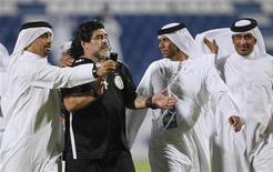 Torcedores do time Al Khor, do Catar, tiram foto com Diego Maradona, técnico do time Al-Wasl após partida da Copa do Golfo, em Doha. Maradona foi empossado como Embaixador Honorário do Esporte de Dubai, menos de dois meses após ser demitido do clube Al Wasl. 30/05/2012 REUTERS/Mohammed Dabbous