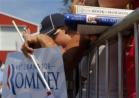 A supporter holds Republican presidential candidate and former Massachusetts Governor Mitt Romney's book ''No Apology'' and a copy of the ''Book of Mormon'' at a campaign rally at the Long Family Orchard and Farm in Commerce, Michigan August 24, 2012. REUTERS/Brian Snyder
