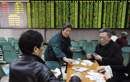 Investors play cards in front of an electronic board showing stock information filled with green-coloured figures, which indicate falling prices, at a brokerage house in Nanjing, Jiangsu province in this March 28, 2012 file photo. The Chinese retail investor trading room, a photogenic anachronism frequented by tea-swilling, day-trading retirees who buy and sell stocks between hands of cards, may soon be gone as brokerages cut costs and move upmarket. Picture taken March 28, 2012. REUTERS/Leo Lang/Files