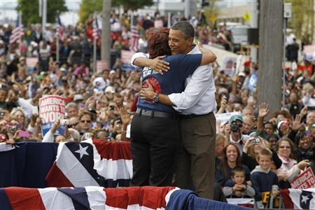 U.S. President Barack Obama hugs union worker Ghana Goodwin Dye as he speaks at a Labor Day event at General Motors Headquarters in Detroit, Michigan, September 5, 2011. REUTERS/Jason Reed
