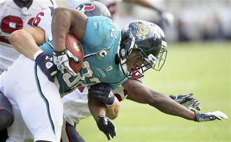 Running back Maurice Jones-Drew of the Jacksonville Jaguars (R) is tackled by the Houston Texans defense during the second half of their NFL football game in Jacksonville, Florida November 27, 2011. REUTERS/Daron Dean