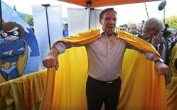 Coalition Avenir Quebec (CAQ) leader Francois Legault does a superman pose after donning a cape while campaigning at a Family Day Festival in Laval, Quebec, September 2, 2012. Quebec voters will go to the polls in a provincial election on September 4. REUTERS/Christinne Muschi