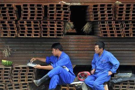 Workers rest on steel pipes at a steel wholesale market in Shenyang, Liaoning province, August 1, 2012. REUTERS/Stringer