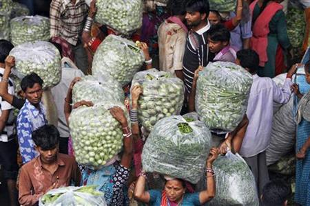 People carry vegetable bags at a wholesale vegetable market in Ahmedabad August 14, 2012. REUTERS/Amit Dave