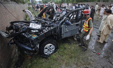 Rescue worker survey a damaged vehicle after it was hit during a bomb attack in Peshawar September 3, 2012. Two Americans working for the U.S. consulate were wounded in a bomb attack on their vehicle in the Pakistani city of Peshawar on Monday, the American embassy said. REUTERS/Khuram Parvez