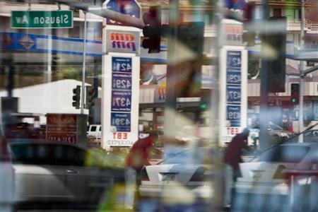 A man refuels his car as gas prices are reflected into the windows of the United Oil gas station in Los Angeles, California March 24, 2012. REUTERS/Bret Hartman