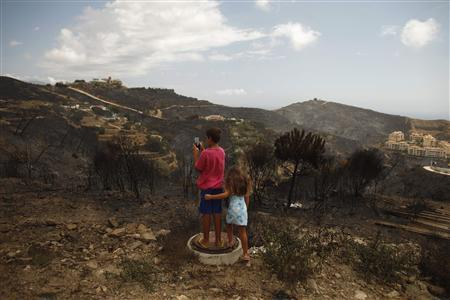 A boy takes a picture with a tablet of a burnt down residential area in Sitio de Calahonda, near Malaga, southern Spain, August 31, 2012. REUTERS/Jon Nazca
