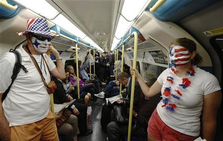 Andy King and Molly Wilson from Michigan in the U.S. travel to the Olympic Park on a London Underground train that is less crowded than usual, during rush hour in London July 30, 2012. REUTERS/Luke MacGregor