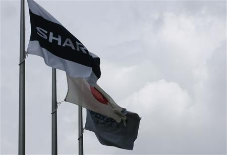 A Sharp Corp flag (L-R), Japanese national flag and Foxconn flag, the trading name of Taiwan's Hon Hai Precision Industry Co., are hoisted at Sharp's Sakai plant in Sakai, western Japan in this August 30, 2012 file photo. REUTERS/Tim Kelly/Files
