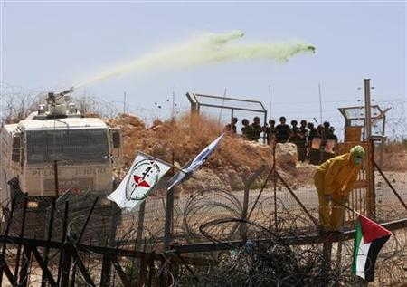 Israeli soldiers use a truck to fire a water cannon containing a foul smelling substance during a protest against the controversial Israeli barrier in the West Bank village of Bilin, near Ramallah July 17, 2009. REUTERS/Darren Whiteside