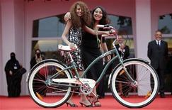 """Diretora da Arábia Saudita Haifaa al-Mansour (D) e atriz Waad Mohammed posam com bicicleta no tapete vermelho em estreia de """"Wajda"""" durante Festival Internacional de Cinema de Veneza. 31/08/2012 REUTERS/Max Rossi"""
