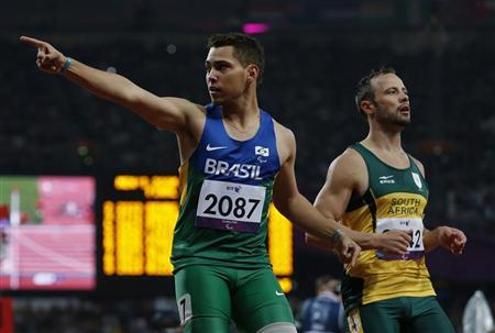 Brazil's Alan Oliveira (L) celebrates in front of South Africa's Oscar Pistorius after winning the men's 200m T44 classification at the Olympic Stadium during the London 2012 Paralympic Games September 2, 2012. REUTERS/Eddie Keogh
