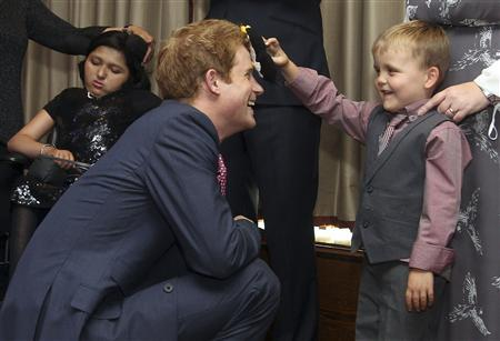 Britain's Prince Harry talks to Alex Logan, aged six, as he attends the WellChild awards ceremony at the InterContinental Hotel in London September 3, 2012. REUTERS/Lewis Whyld/pool