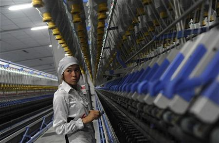 An employee works at the production line of a textile mill in Aksu, Xinjiang Uighur Autonomous Region July 25, 2012. REUTERS/Stringer