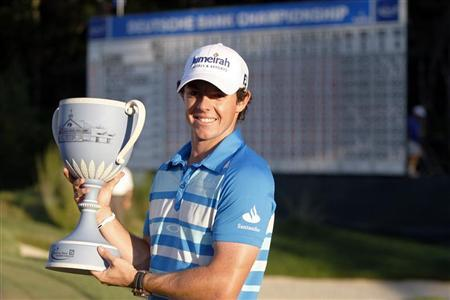 Rory McIlroy of Northern Ireland lines holds up the championship cup at the 18th hole after winning in the final round of the Deutsche Bank Championship golf tournament in Norton, Massachusetts September 3, 2012. REUTERS/Dominick Reuter (