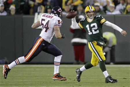 Chicago Bears linebacker Brian Urlacher (L) chases Green Bay Packers quarterback Aaron Rodgers (R) in the first half during their NFL football game in Green Bay, Wisconsin December 25, 2011. REUTERS/Darren Hauck