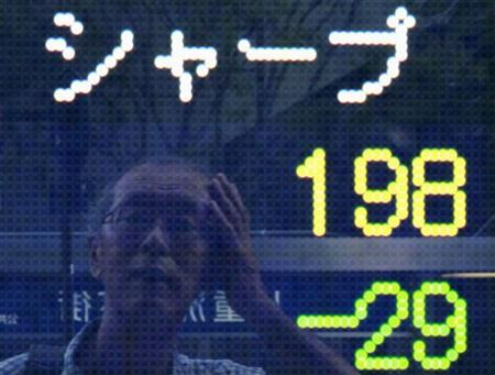 A man is reflected on an electronic board displaying the closing share price of Sharp Corp outside a brokerage in Tokyo August 31, 2012. REUTERS/Yuriko Nakao