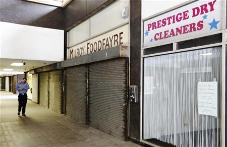 A man walks through a stretch of closed-down and empty shops in central London July 30, 2012. REUTERS/Luke MacGregor