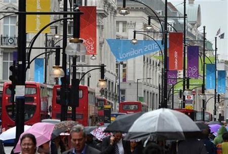 Shoppers hold umbrellas as they walk under London Olympic 2012 banners in Oxford Street in central London July 18, 2012. REUTERS/Toby Melville