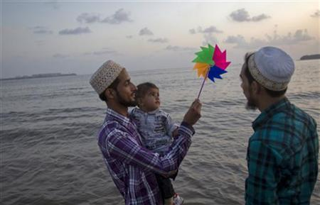 Mohammed (L), 25, holds a paper windmill aloft as he wades in the waters of the Arabian Sea with his son Mortaza and brother Taher in Mumbai September 23, 2011. REUTERS/Vivek Prkash/Files
