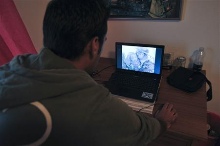 Ali Jamal, 24, an asylum seeker from Syria, looks at pictures from his country on a laptop in his room at a hostel in Koepingebro near Ystad August 30, 2012. REUTERS/Markus Kinnunen