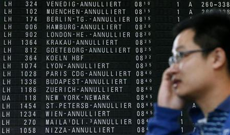 A passenger talks on his mobile phone as he stands in front of a flight schedule board displaying cancelled flights of German air carrier Lufthansa at the Fraport airport in Frankfurt, September 4, 2012. REUTERS/Kai Pfaffenbach
