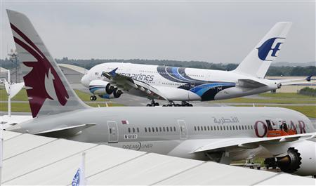 An Airbus A380, owned by Malaysia Airlines, lands behind a Boeing 787, owned by Qatar Airways, ahead of the Farnborough Airshow 2012 in southern England in this July 8, 2012 file photograph. REUTERS/Luke MacGregor/Files