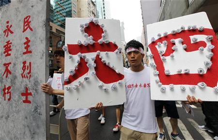 A student protester carrying a board walks next to a mock tombstone, symbolizing those who died during the June 4 military crackdown on the pro-democracy movement at Beijing's Tiananmen Square 23 years ago, during a march in Hong Kong May 27, 2012. REUTERS/Tyrone Siu