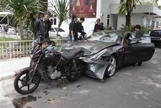 Policemen examine a damaged Ferrari at the home of the late Red Bull founder Chaleo Yoovidhaya in Bangkok September 3, 2012. REUTERS/Stringer