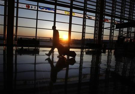 A traveller walks to his flight at Ronald Reagan National Airport as the sun rises in Washington, September 24, 2008. REUTERS/Jason Reed
