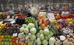 Женщина продает овощи и фрукты на рынке в центре Санкт-Петербурга, 9 июня 2011 г. Инфляция в РФ в приблизилась в августе к целевому ориентиру ЦБР на 2012 год, достигнув 5,9 процента в годовом выражении по сравнению с 5,6 процента в июле и 8,2 процента за аналогичный период 2011 года, на фоне роста продовольственных цен на мировых рынках, засухи в части регионов РФ, ослабления рубля и эффекта базы прошлого года. REUTERS/Alexander Demianchuk