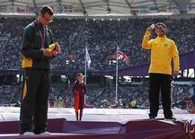 Medalhista de ouro Alan Oliveira (D), do Brasil, posa ao lado do sul-africano Oscar Pistorius, que levou a prata, no pódio durante cerimônia de vitória dos 200 metros rasos das Paralimpíadas de Londres. 03/09/2012 REUTERS/Stefan Wermuth