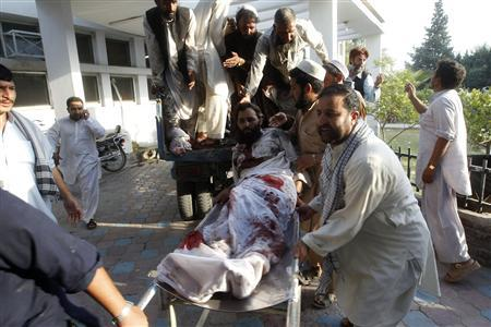 Afghan men carry a man injured in a bomb blast to a hospital in Jalalabad September 4, 2012. A suicide bomber blew himself up at a funeral in eastern Afghanistan on Tuesday, killing at least 20 people and wounding dozens, officials said, one of the biggest attacks on civilians in weeks. REUTERS/ Parwiz