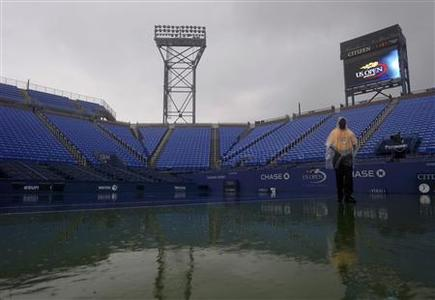 A man walks courtside during a downpour at the U.S. Open tennis tournament in New York September 4, 2012. REUTERS/Ray Stubblebine