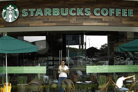 A customer with a cup of coffee leaves the new Starbucks store in San Jose June 20, 2012. REUTERS/Juan Carlos Ulate