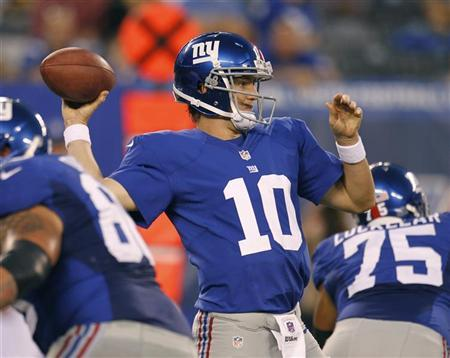 New York Giants quarterback Eli Manning looks to pass while under pressure by the New England Patriots during their NFL preseason football game in East Rutherford, New Jersey, August 29, 2012. REUTERS/Gary Hershorn