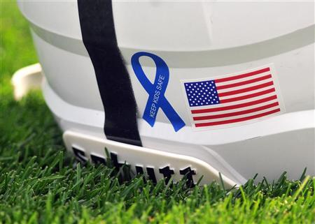 A Penn State helmet sits on the turf before their NCAA football game against Ohio University in State College, Pennsylvania September 1, 2012. The ribbon is a new addition to the helmets this year in response to the Jerry Sandusky child sexual abuse case. REUTERS/Pat Little