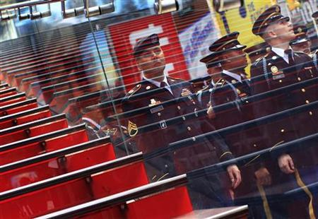 U.S. Army troops are reflected in the window of a doubledecker bus during the Army's 237th anniversary celebrations at Times Square in New York June 14, 2012. REUTERS/Shannon Stapleton